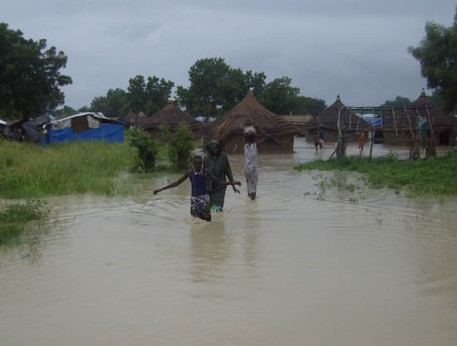 Bor flood victims wade through a lake of flood plains in Bor town.